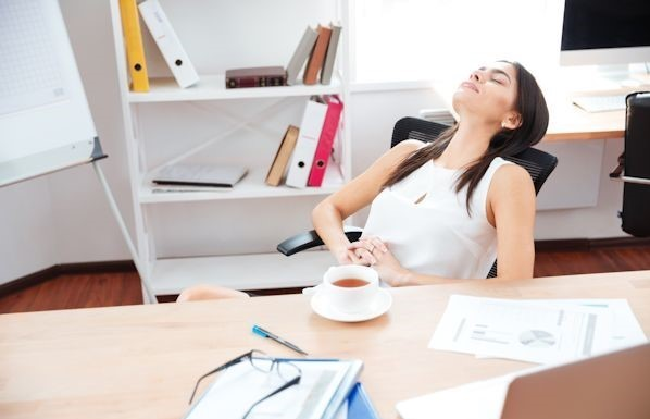 Beautiful businesswoman relaxing at her workplace in office